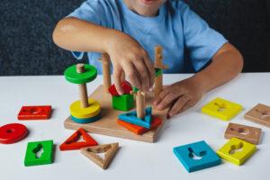 criança brincando com brinquedo de empilhar torre geométrica formas coloridas